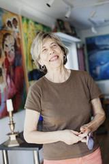 Smiling senior female artist holding paint brushes in studio