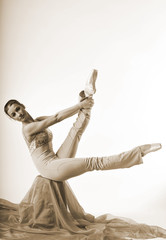 sports girl in a ballet hall in complex poze.balerina warming up, light tones picture. daylight falls on the blonde