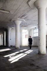 Man standing in old building with columns