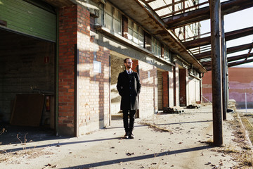 Lonely businessman in front of abandoned industrial building