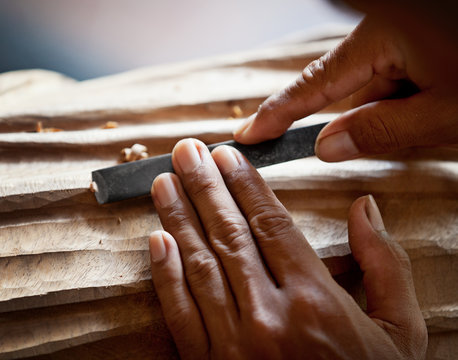 Hands woodcarver with the tool close-up