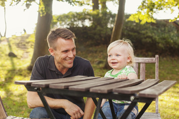 Happy man looking at son sitting on chair in park