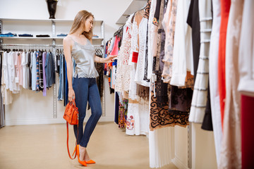 Woman standing and choosing clothes in clothing store