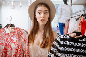 Confused woman choosing dress in clothing store