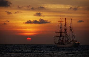 Old sailing ship in the sea at sunset. Barquentine