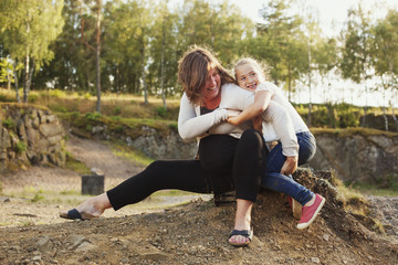 Playful pregnant woman enjoying with daughter in forest