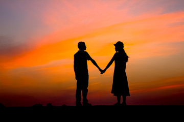 The silhouette of beautiful young couple posing at sunset