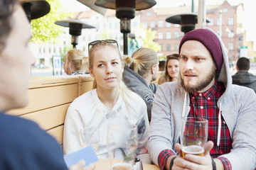 Man looking at friend while holding beer glass