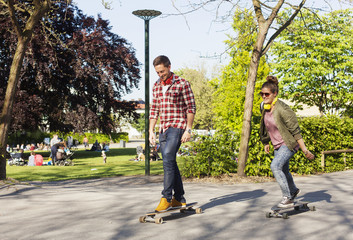 Full length of happy couple skateboarding on street at park