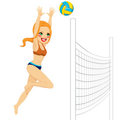 Beautiful red haired volleyball woman player jumping to hit the ball over the net