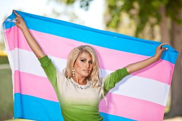 Latina Transgender female holding pride flag over and behind her head.