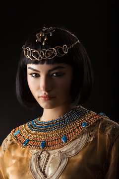 Beautiful woman like Egyptian Queen Cleopatra with serius face on black background