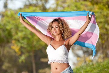 Transgender female proud holding pride flag over and behind her head.