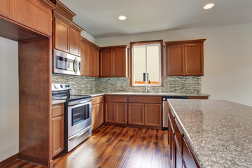 Modern kitchen room with brown cabinets, granite counter tops and hardwood floor.