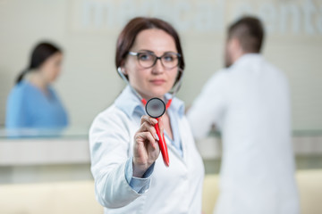 Portrait of woman doctor at hospital corridor, looking at camera.