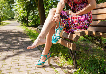 woman holding a shoe sitting on a park bench