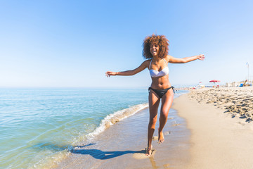 Young black woman having fun at seaside