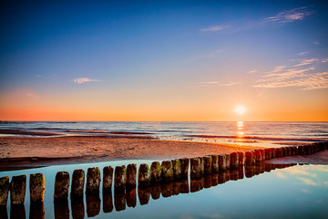 Sunset at Baltic sea, view on old breakwater piles.