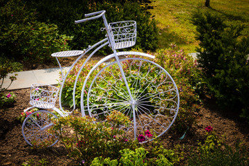 Metal sculpture of bicycle as flowerbed in the garden.