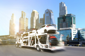 The trailer transports  new cars on highway with big city background use for transportation industry or automotive industry