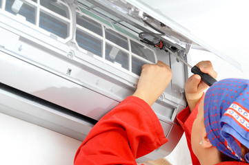 Young woman worker adjusting air conditioner system