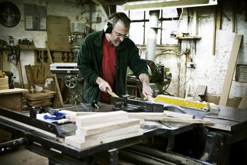A man working in a furniture maker's workshop.