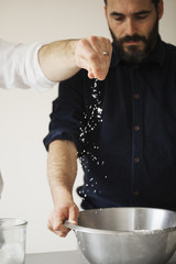 Two bakers standing at a table, baking bread, sprinkling salt into a metal mixing bowl.