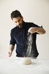 Baker standing at a table, liberally sprinkling flour over bread dough.