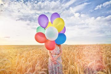 Frau im Feld mit Luftballons
