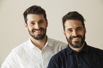 Portrait of two bearded men smiling at the camera.