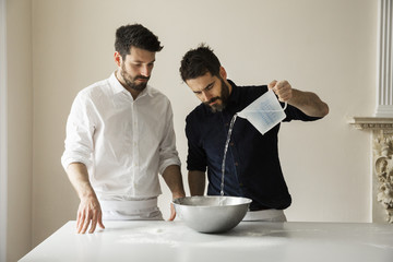 Two bakers standing at a table, preparing bread dough, pouring water from a measuring jug into a metal mixing bowl.
