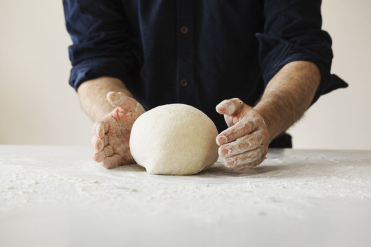 Close up of a baker kneading and shaping bread dough into a ball.