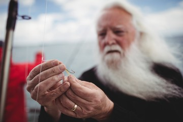Close up of fisherman adjusting fishing hook