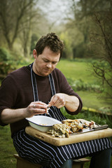 Chef sitting outdoors with a chopping board on his lap, preparing a crab.