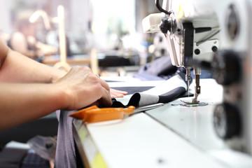 Maszyna do szycia. Zakład produkcyjny,szycie odzieży przez szwaczki  na maszynie do szycia