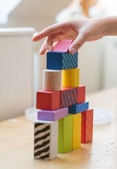 Child hand playing with toy blocks.