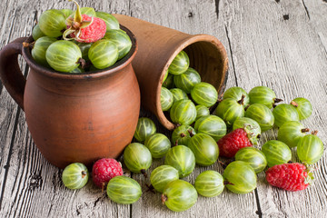 Freshly picked raspberries and gooseberries.    Freshly picked raspberries and gooseberries in a clay mug and in a glass on a wooden table.