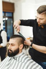 Dark haired barber doing a haircut