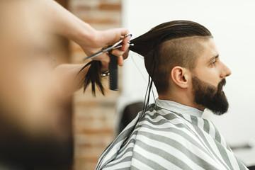 Man with dark hair doing a haircut