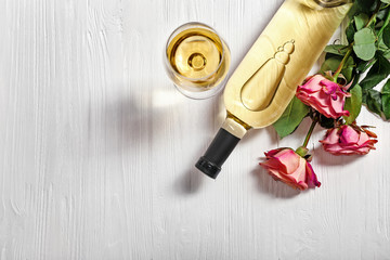 Bottle of wine, glass and roses on a wooden background