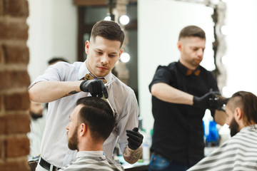 Barbers doing haircuts for clients
