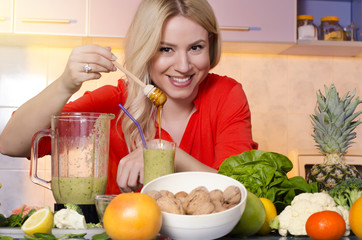 Happy gorgeous, healthy woman putting honey in freshly made smoothie