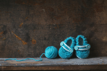 Crochet baby booties with blue yarn on a wooden shelf.