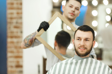 Barber holding a mirror for client