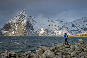Hiker standing on rocks looking at view of snow covered mountian