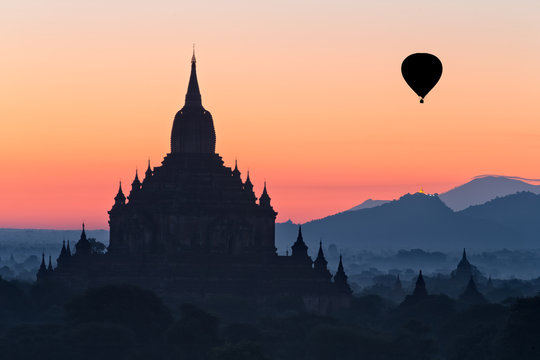 Silhouette of temple and hot air balloon at dawn, Myanmar