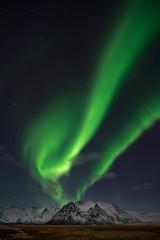 Aurora borealis over snow covered mountain
