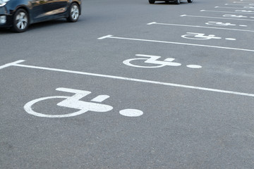 Empty parking places with handicapped or disabled signs on asphalt and detail of moving cars