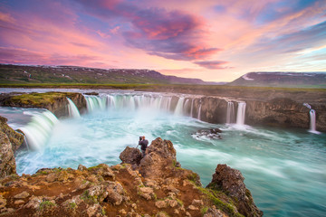 Photographer photographing godafoss waterfall, iceland