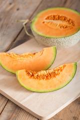 Fresh melon sliced on wooden board.